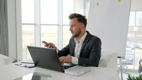 Homem de negócios bem sucedido Works no portátil no Internet na sala de reuniões, conversa executiva feliz no smartphone vídeos de arquivo