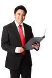 Homem de negócios bonito com uma prancheta que veste uma camisa e um laço brancos Fotos de Stock Royalty Free