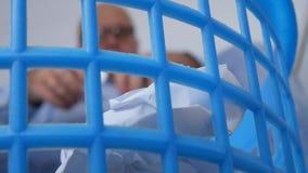 Homem de negócios borrado no escritório que joga pedaços de papel amarrotados na cesta do lixo filme