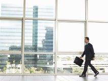 Homem de negócios With Briefcase Walking no escritório Foto de Stock Royalty Free