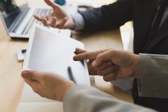 Homem de negócios And Businesswoman que usa uma tabuleta digital para discutir imagens de stock