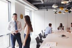Homem de negócios And Businesswoman Standing na sala de reuniões moderna que tem a discussão informal com os colegas que encontra foto de stock royalty free
