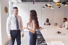 Homem de negócios And Businesswoman Standing na sala de reuniões moderna que tem a discussão informal com os colegas que encontra fotografia de stock
