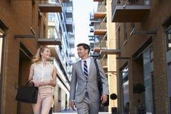Homem de negócios And Businesswoman Walk a trabalhar através da rua da cidade fotos de stock