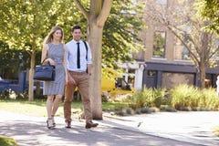 Homem de negócios And Businesswoman Walk a trabalhar através do parque da cidade fotografia de stock royalty free
