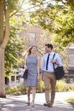 Homem de negócios And Businesswoman Walk a trabalhar através do parque da cidade fotografia de stock