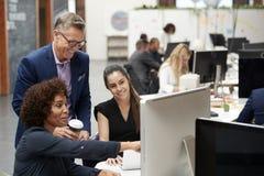 Homem de negócios And Businesswomen Working no computador na mesa no escritório de plano aberto imagem de stock
