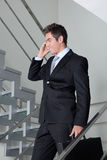 Homem de negócios On Call Walking abaixo das escadas fotografia de stock