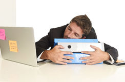 Homem de negócios cansado e desperdiçado novo que trabalha no esforço no sono do laptop do escritório esgotado fotografia de stock