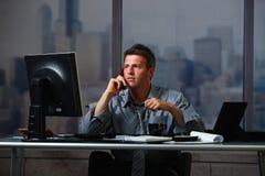 Homem de negócios na chamada que trabalha fora do tempo estipulado Foto de Stock