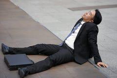 Homem de negócios cansado ou fatigante que senta-se no assoalho após o incêndio Fotografia de Stock Royalty Free