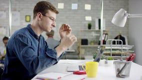 Homem de negócios cansado produtivo que inclina o trabalho de escritório para trás de terminação no portátil, gerente eficaz sati video estoque
