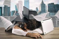 Homem de negócios cansado que dorme sob uma pilha dos portáteis devido à carga de trabalho imagens de stock