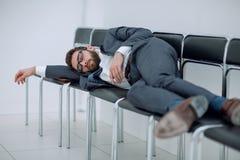 Homem de negócios cansado que encontra-se em cadeiras e que espera uma entrevista fotos de stock