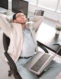 Homem de negócios cansado que senta-se na frente de sua mesa fotografia de stock royalty free
