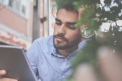 Homem de negócios cansado que trabalha na tabuleta digital no café da rua fotos de stock royalty free