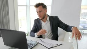 Homem de negócios cansado, sobrecarregado no escritório, homem de negócios irritado com o portátil pela tabela, gerente novo que  video estoque