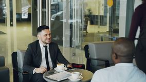Homem de negócios caucasiano alegre na roupa formal que sorri e que discute o lucro de negócio com seu afro-americano vídeos de arquivo