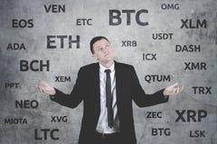Homem de negócios caucasiano confundido com os símbolos do cryptocurrency fotografia de stock royalty free