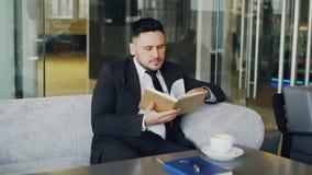 Homem de negócios caucasiano esperto na roupa formal que lê o livro de texto com e que bebe o café no café elegante na pausa para video estoque