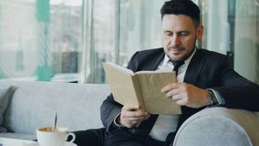 Homem de negócios caucasiano esperto na roupa formal que lê o livro de texto com e que bebe o café no café elegante na pausa para filme
