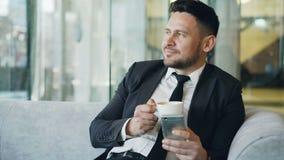 Homem de negócios caucasiano feliz na roupa formal que sorri e que olha sua tela do smartphone ao beber o café em pairoso video estoque