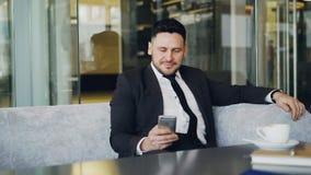 Homem de negócios caucasiano feliz na roupa formal que sorri e que olha sua tela do smartphone ao beber o café em pairoso vídeos de arquivo