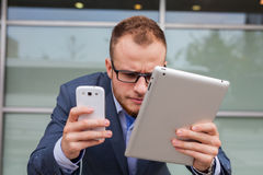 Homem de negócios caucasiano fora do escritório usando o telefone celular e o tabl Imagem de Stock