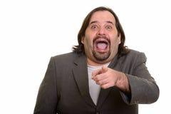 Homem de negócios caucasiano gordo feliz que sorri ao rir e ao ponto fotografia de stock