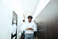 Homem de negócios caucasiano novo que faz um telefonema ao andar ao longo do corredor imagens de stock royalty free