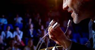 Homem de negócios caucasiano que fala no seminário do negócio sobre a fase no auditório 4k filme