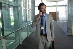 Homem de negócios caucasiano que fala no telefone celular ao andar no corredor fotografia de stock royalty free