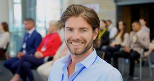 Homem de negócios caucasiano que sorri e que senta-se no seminário 4k do negócio video estoque