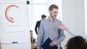Homem de negócios caucasiano de sorriso profissional novo que motiva empregados incorporados felizes no diagrama das vendas da re video estoque