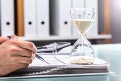 Homem de negócios Checking Bill With Hourglass On Desk fotos de stock