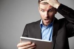 Homem de negócios chocado com tabuleta digital Fotos de Stock Royalty Free