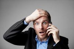 Homem de negócios chocado que fala no telefone fotos de stock