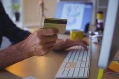 Homem de negócios colhido que compra em linha com o cartão de crédito no escritório fotos de stock royalty free