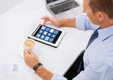 Homem de negócios com ícones do app no PC e no café da tabuleta Foto de Stock