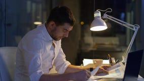 Homem de negócios com arquivos e funcionamento do portátil na noite filme