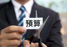 Homem de negócios com as tesouras que cortam Bu do chinês da etiqueta Imagens de Stock