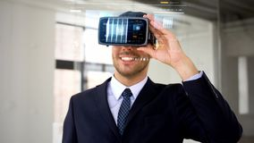 Homem de negócios com auriculares e cubo do vr na tela video estoque