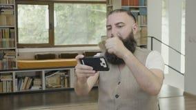 Homem de negócios com a barba que veste o equipamento ocasional que senta-se no escritório que olha sua leitura do smartphone e q video estoque