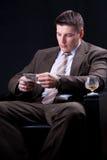 Homem de negócios com bebidas e contagem do dinheiro Fotos de Stock