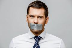 Homem de negócios com a boca selada fita Fotografia de Stock Royalty Free