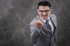 Homem de negócios com braço acima no fundo concreto cinzento fotografia de stock