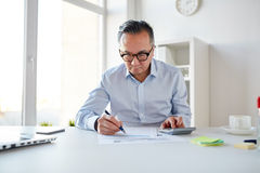 Homem de negócios com calculadora e papéis no escritório imagens de stock