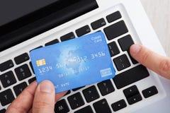 Homem de negócios com cartão de crédito que deposita em linha na mesa imagem de stock royalty free