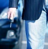 Homem de negócios com chave e carro Imagens de Stock
