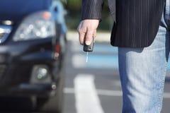 Homem de negócios com chave e carro Fotos de Stock Royalty Free